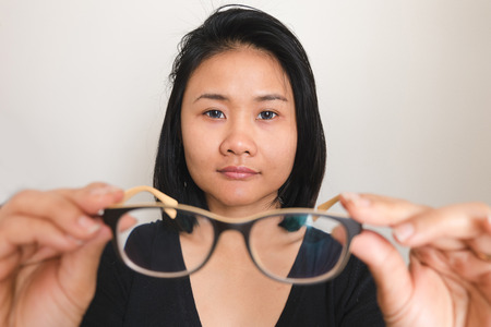 asian woman taking off glasses, picking glasses Stock Photo