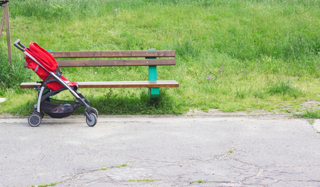 posterity: Empty red stroller next to the bench in the park Stock Photo