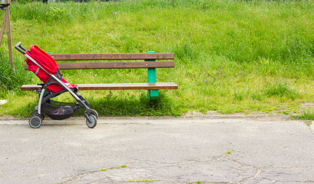 urban parenting: Empty red stroller next to the bench in the park Stock Photo