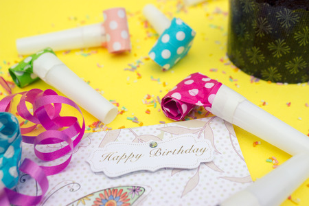 Party horns (whistles) and happy birthday card on yellow background