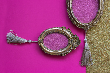 Two vintage golden oval picture frames on pink and golden background, with copy space in the frame   Stock Photo