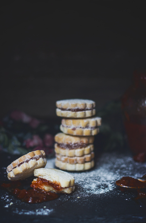Stack of homemade vanilla jam cookies, on dark background, with copy space 写真素材