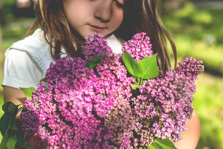 Little girl with bouquet of lilac in her hands