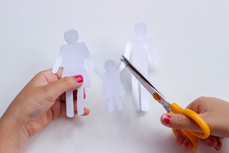 Hands of a little girl cutting paper chain family with scissors; broken family or divorce concept