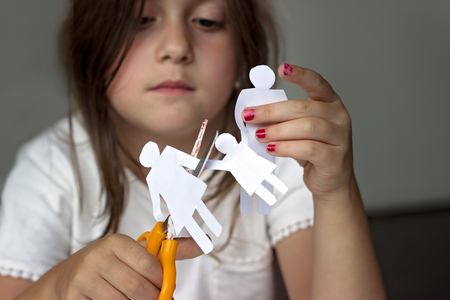 Sad little girl with paper family and scissors; divorce or family problems concept