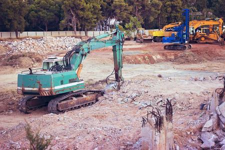 Big green excavator at construction site
