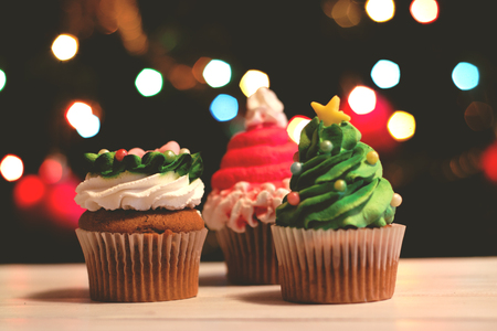 Cupcakes decorated for christmas, against colorful bokeh background; holiday background Stock Photo