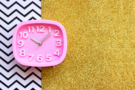 Pink alarm clock on golden and chevron  background