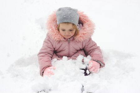Little girl is sitting in the snow, playing with fresh snow that fell over night Imagens
