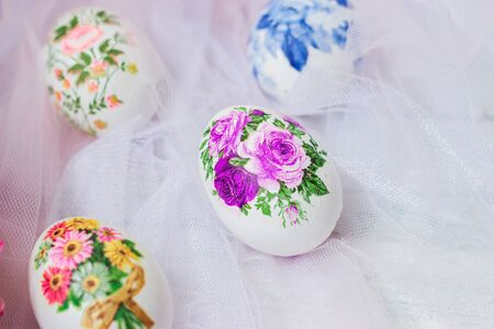 Decorated Easter eggs and flowers on white tulle background; decoupage technique