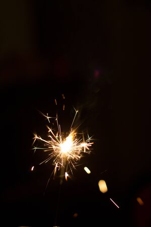 Burning party sparkler on black background