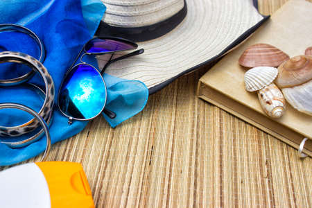 Beach concept-sun glasses, flip flops, book and sea shell