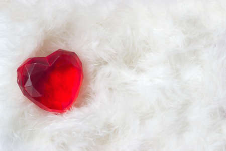 Valentines day background - red heart in white feathers background