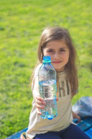 Little girl holds bottle of water