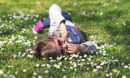 Little girl enjoys day in the park, laying on grass Standard-Bild