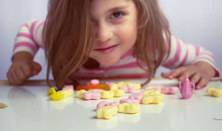 Little girl playing with candies; shallow depth of field