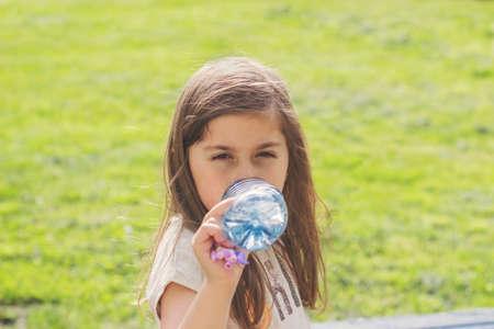 Little girl drink water from plastic bottle