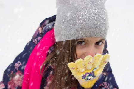 Little girl eating snowflakes from her gloves