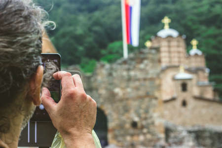 Man taking a photo of a Serbian ortodox monastery Ravanica, built in 14th century