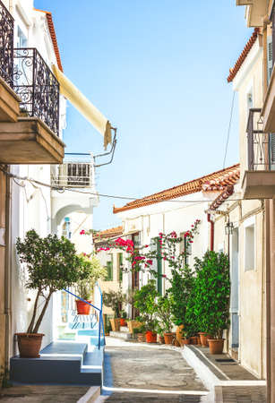 Narrow streets of Neorio town in Poros island, Greece;  Old white houses with flowers