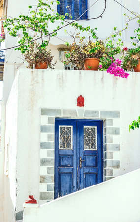 Narrow street in Neorio town on Poros island, Greece. Old white house with blue door and flowers