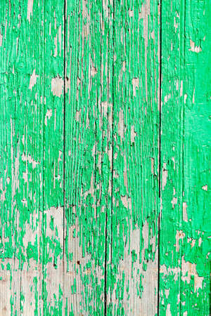 Close up of a old wooden door, green paint peeling off; texture background