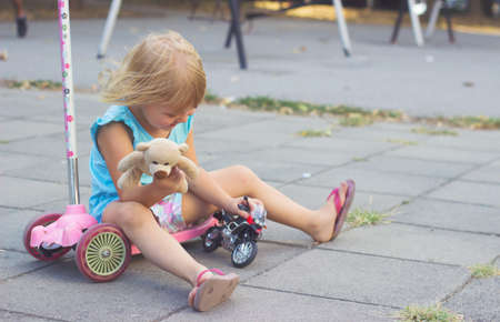 Little girl sitting on her scooter, playing with toys