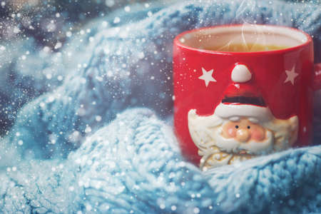 Winter background - red cup with santa claus and woolen scarf Stock fotó