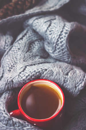 Winter background - hot tea in red cup and gray woolen scarf Stock fotó