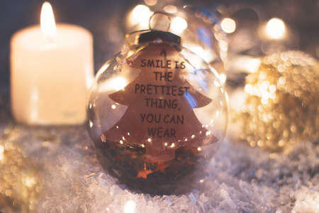 """Christmas and new year decoration - glass ornament with quote """"a smile is the prettiest thing you can wear"""", candle and christmas lights on wooden table"""