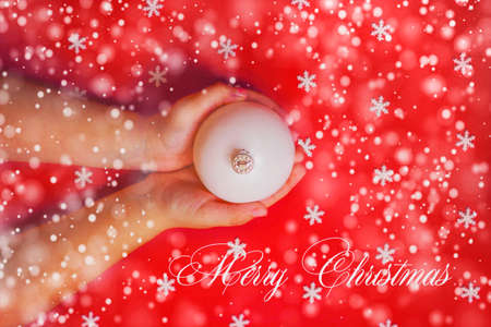 Merry Christmas background or gift card - child's hands holding white ornament on red background Stock fotó