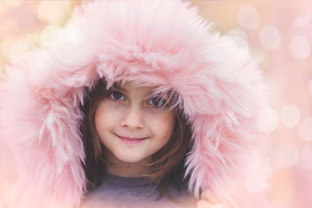 Portrait of a beautiful little girl with pink fur hood Standard-Bild - 157542347