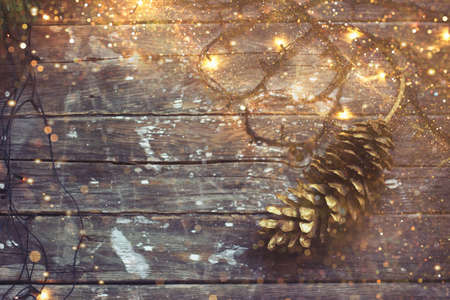 Christmas background - christmas lights and pine cone on dark wooden background, with golden glitter Stock fotó