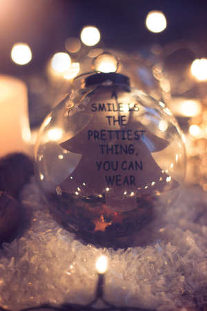 """Christmas and new year background - glass ball with quote """"a smile is the prettiest thing you can wear"""", candle and christmas lights on wooden table"""
