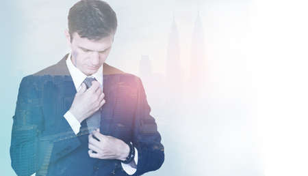 Dual exposure of a young businessman before his meeting, setting his tie and suit, city background; business concept, copy space