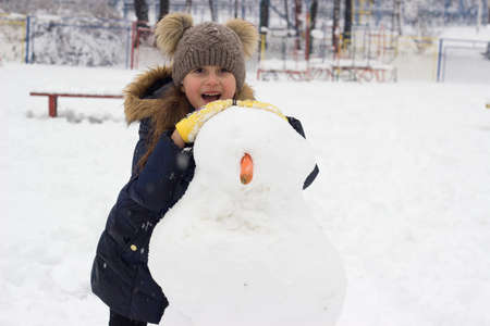 Little girl having fun, making snowman; winter background with copy space