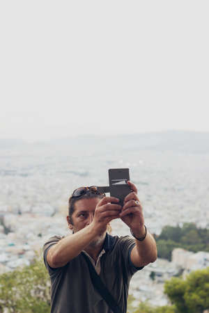 Man is taking a selfie on the hill, cityscape is in the background