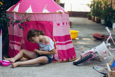 Little girl sitting in backyard, playing in tent; Standard-Bild
