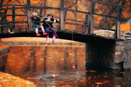 Two little girls sitting on wooden bridge and pretend fishing; autumn background
