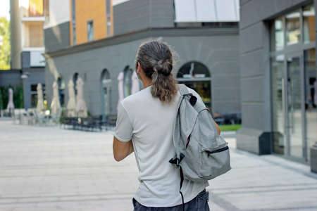 Middle aged man with gray backpack on the street; with copy space Standard-Bild