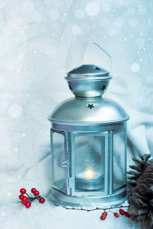 Christmas lantern with snowfall; Christmas background with pine cones and holly berries