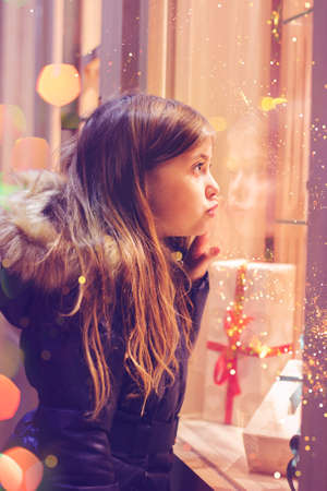 Beautiful little girl in front of confectionery shop, decorated with wrapped gift boxes and candies. Christmas concept, window shopping