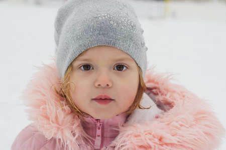 Beautiful little girl, looking at camera, winter portrait