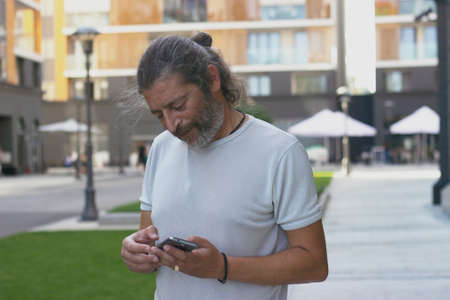 Middle aged man standing on the street, checking his smartphone