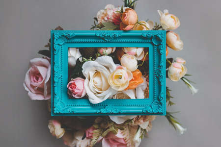 Composition made of photo frame and artificial flowers in pastel colors