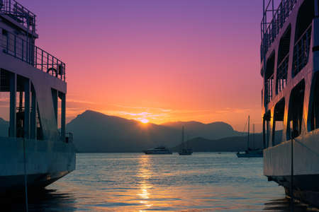 Ferryboats docked in marina, beautiful pink sky in the background; summer/travel background with copy space