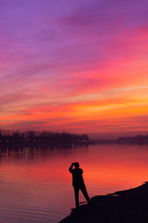 Silhouette of a man taking a photo of a beautiful sunset sky; With copy space