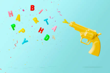 Yellow pistol shooting colorful birthday candles and colorful confetti, against  blue background. Happy birthday  concept with copy space