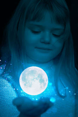 Little girl holding the moon and stars on the palm of her hand