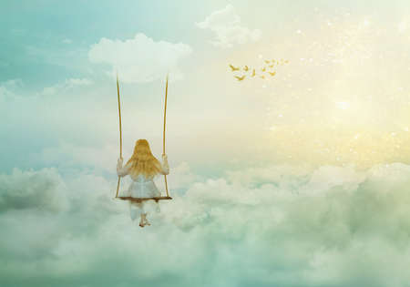 Lonely girl sitting on the swing above clouds; fantasy/solitude/surreal background with copy space Standard-Bild